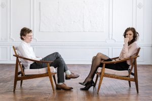 A couple sit across from one another as they ignore eachother. Contact a couples therapist in Pasadena, CA for support with marriage counseling in Pasadena, CA