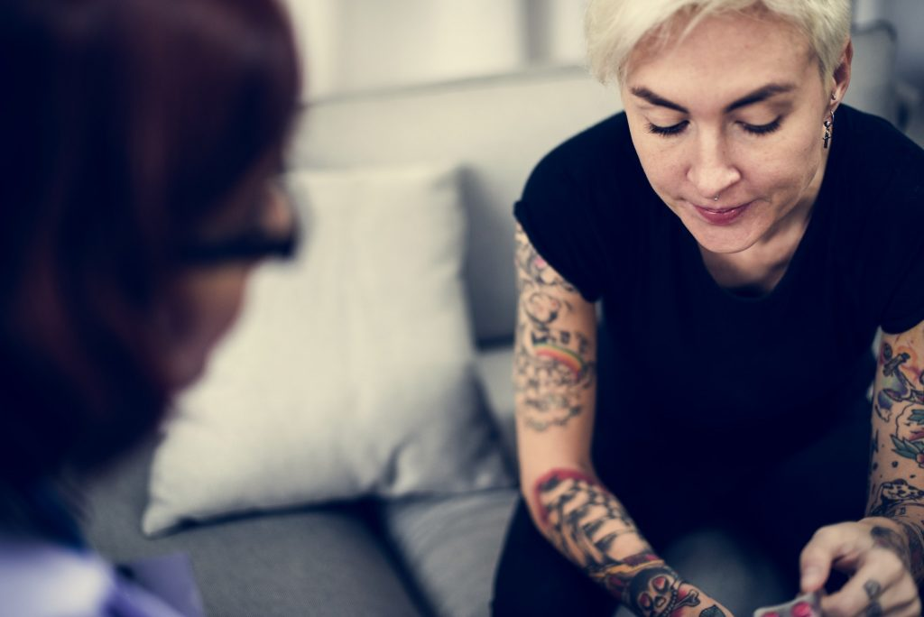 A tattooed woman listens to a woman with glasses. This could represent how couples therapy and marriage counseling in Pasadena, CA can help repair relationships. Contact a marriage counselor to learn about infidelity counseling and other services.