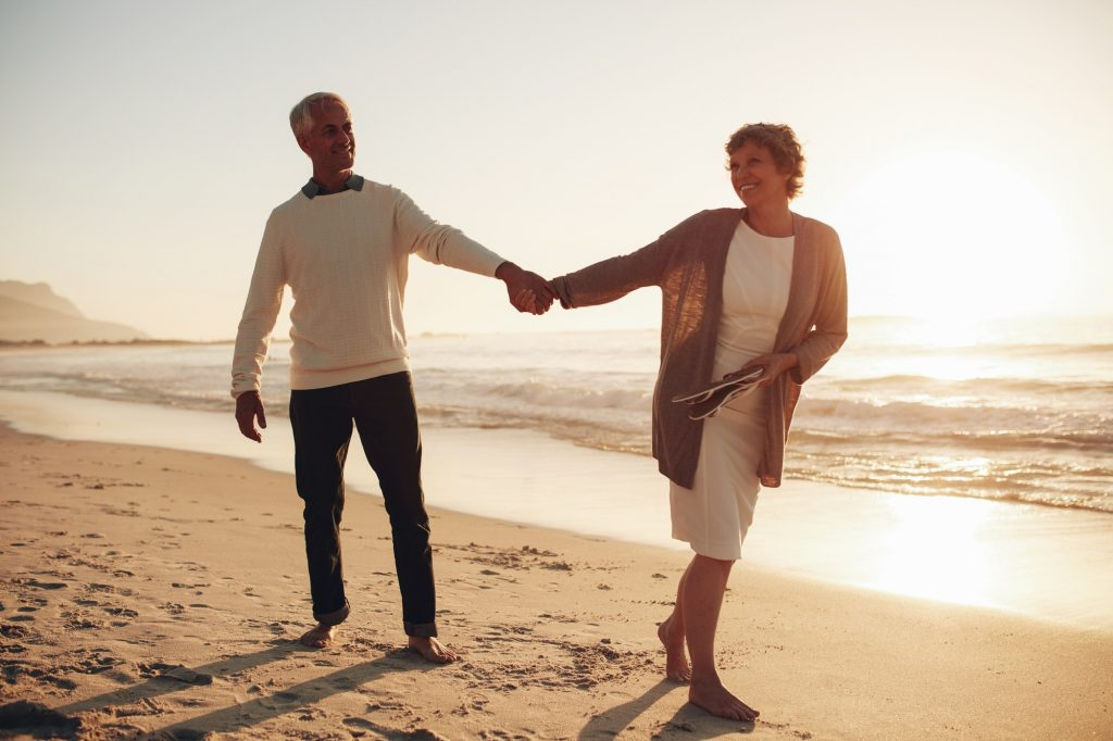 A middle aged couple hold hands as they walk along the beach. This symbolizes the benefits of couples therapy and marriage counseling in Pasadena, CA. Contact a marriage counselor to learn more about marriage counseling in Pasadena, CA for support! 91101 | 95814 | 95688 | 95765