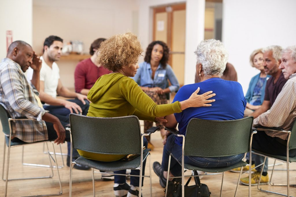 A group of people comfort one another while sitting in a circle. This could represent group therapy in Pasadena, CA. Contact us to learn about our LGBTQ support group, sexual abuse support group, and other services.