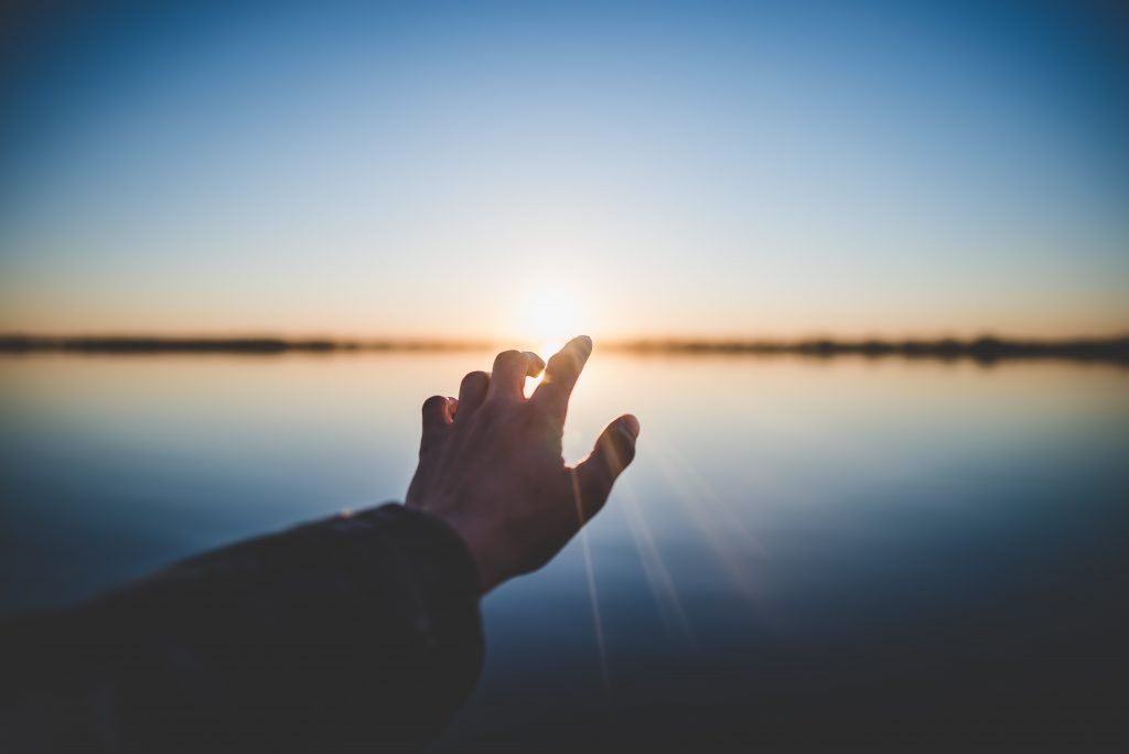 A hand reaches for the rising sun over a body of water. This could represent overcoming past trauma with a trauma therapist in Pasadena, CA. Contact us for trauma therapy in Pasadena, CA, PTSD treatment, and other services. 95630 | 95688 | 95765