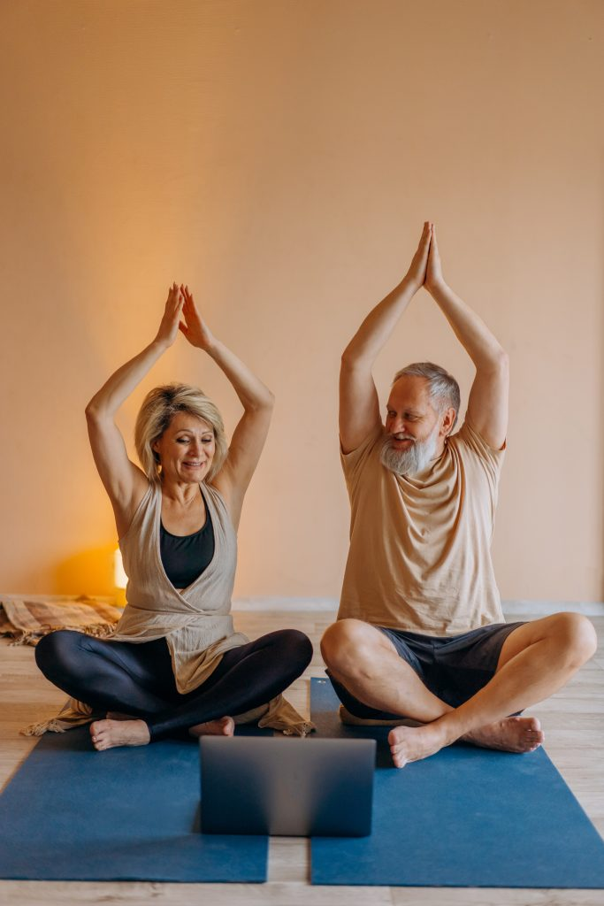 An older couple sit together as they practice yoga. This could represent the importance of the mind body connection. Contact a somatic experiencing therapist for support. Somatic therapy in Los Angeles, CA 91101 | 90026 | 90042 | 90065