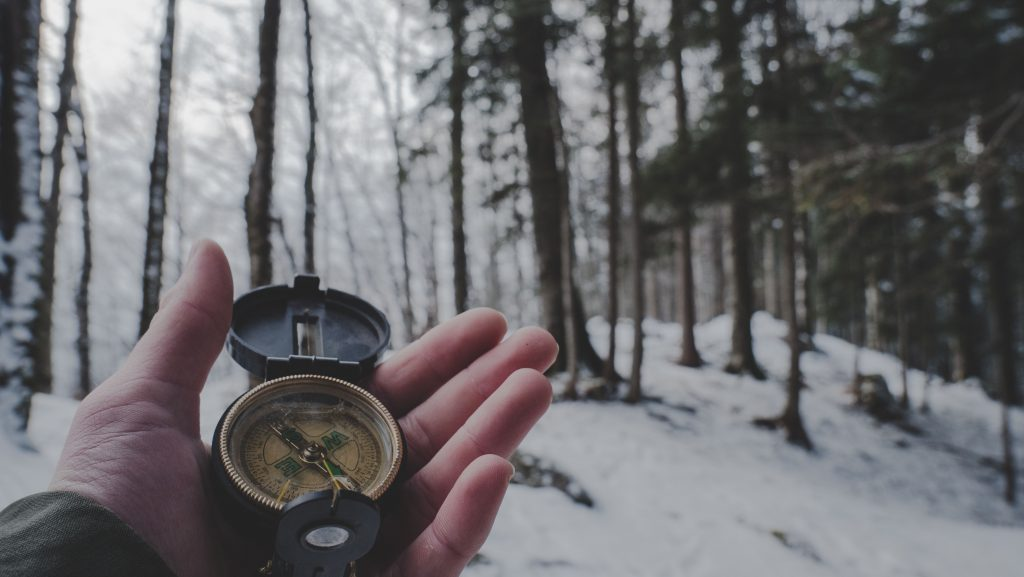 A hand holds a compass as they walk through a snow covered forest. This could represent finding an individual therapist in Pasadena, CA. Contact us to learn about individual therapy for relationship issues and other services.