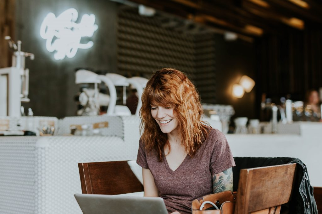 A smiling woman sits in a coffee shop with laptop in lap. This could represent online therapy in California. An online therapist can help with online depression therapy and other services.
