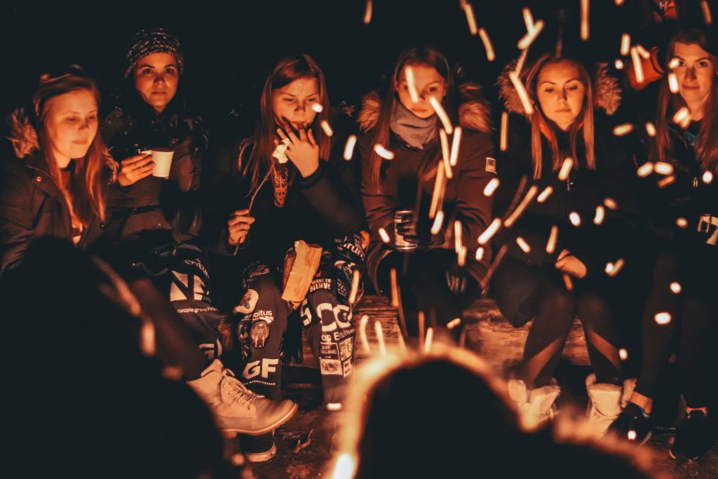 A group of woman sit around a campfire as they roast marshmallows. This represents group therapy in Pasadena, CA. Contact us today to learn more about our sexual abuse support group, group trauma therapy, and other services!