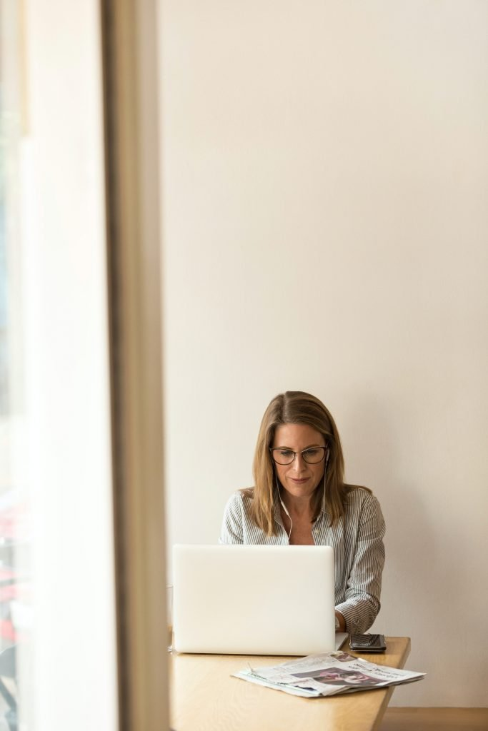 A woman sits at a desk against a blank wall as she types on her laptop. Contact an online therapist in California for support with online therapy wherever you are in the state!