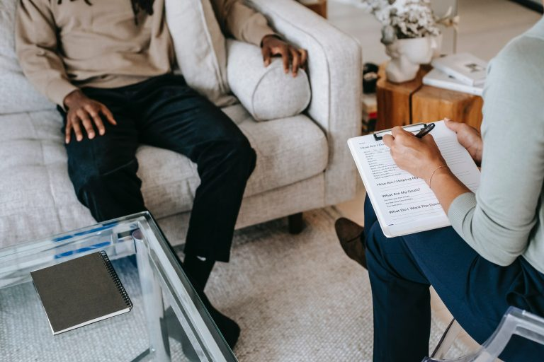 A man sits on a sofa as a therapist across from them writes on their clipboard. This could represent individual therapy in Pasadena, CA. Contact an individual therapist to learn more about individual therapy for relationship issues in Sacramento, CA and other services.