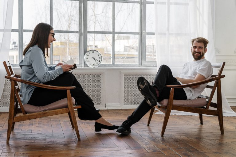 Two people sit in chairs across from one another as they share a laugh. This could represent progress being made with individual therapy and affair recovery counseling in Pasadena, CA. Contact an individual therapist for support with affair recovery and other services.