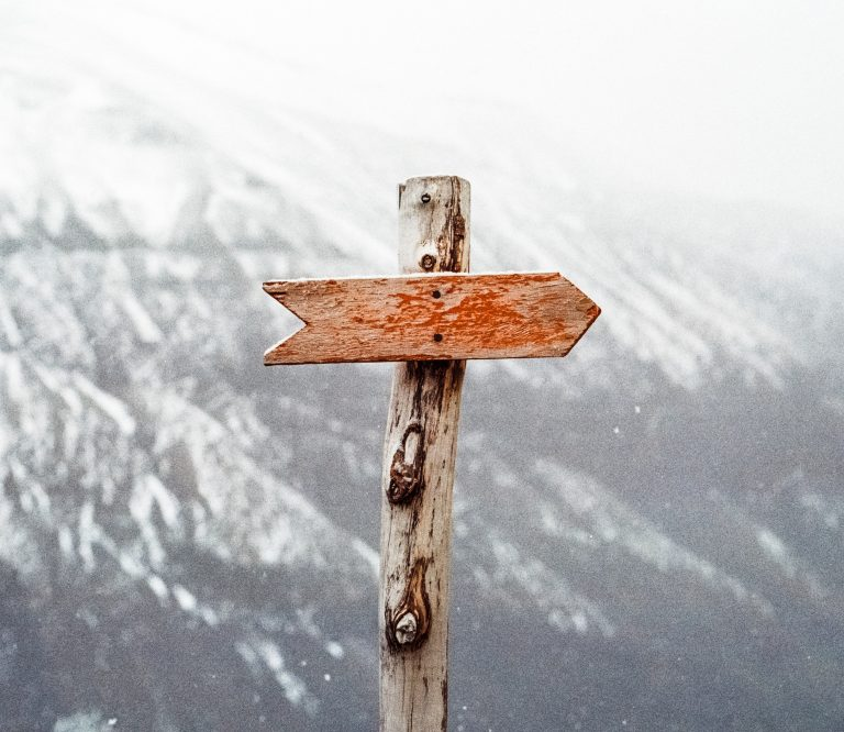 A wooden sign arrow points to the left on a snowy mountain trail. This could represent the help of a individual therapist. Contact our practice to learn more about individual therapy in Pasadena, CA, individual therapy for depression, and other services.