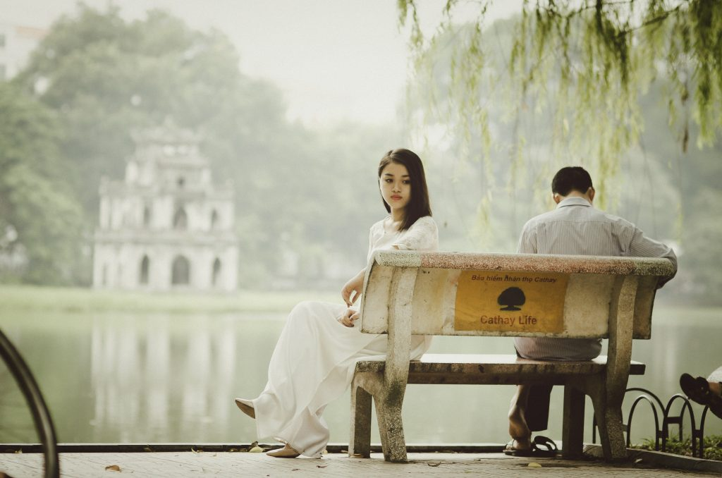 A couple sit on a park bench next to a lake facing away from one another. This could represent the pain of affair recovery. Learn more about affair recovery in Sacramento, CA or affair recovery in Pasadena, CA from an affair recovery therapist in Sacramento, CA. Affair recovery counseling can help your relationship survive & thrive. 95814   95688   95765
