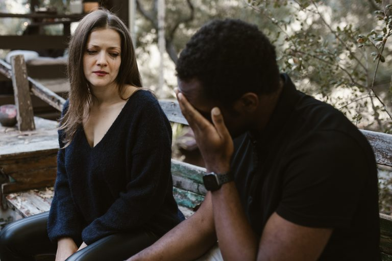 A man hides his face in his hands as his partner watches. Affair recovery counseling in Pasadena, CA can help your relationship recover after an affair. Learn more from an infidelity therapist for more information.
