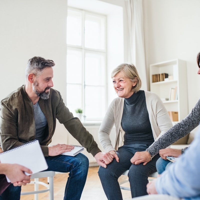 Men and women sitting in a circle and holding hands and smiling. This could represent group therapy in Pasadena, CA. Contact us to learn about group trauma therapy, LGBTQ support groups, and other services to help you!